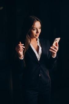 Zakenvrouw die aan de telefoon praat en 's avonds laat op kantoor blijft