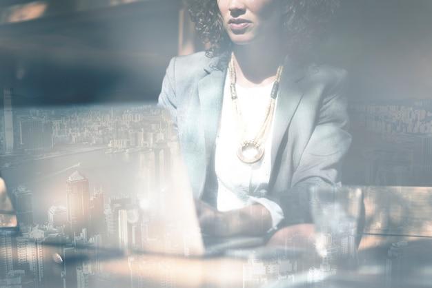 Zakenvrouw die aan een laptop-stadsachtergrond werkt