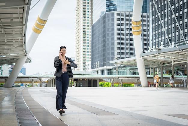 Zakenvrouw die aan het praten over mobiele telefoon kijkt om horloge aan de hand te houden met kantoorgebouwen op de achtergrond