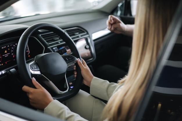Zakenvrouw die auto kiest, autoshowroomverkoper die in de auto zit met de klant en design toont