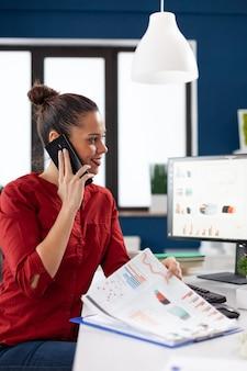 Zakenvrouw die belt met een smartphone die aan het bureau zit