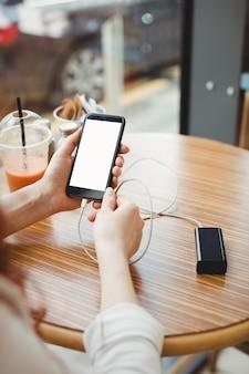 Zakenvrouw die draagbare powerbank gebruikt om haar telefoon in cafetaria op te laden
