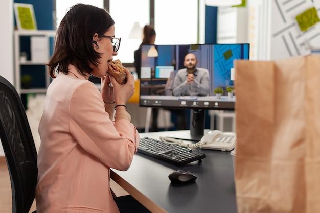 Zakenvrouw die een afhaalmaaltijdenbroodje eet tijdens een online videocall-conferentievergadering die met een externe collega bespreekt. manager zit aan het bureau met afhaalmaaltijden op kantoor