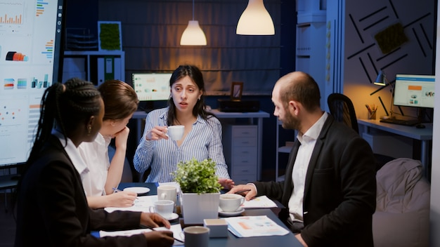 Zakenvrouw die een kopje koffie vasthoudt terwijl ze praat met multi-etnisch teamwork om een managementproject op te lossen met behulp van grafiekenpapier. diverse collega's die 's avonds laat in de vergaderruimte werken