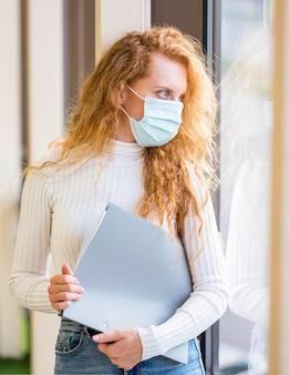 Zakenvrouw die een masker draagt en documenten vasthoudt