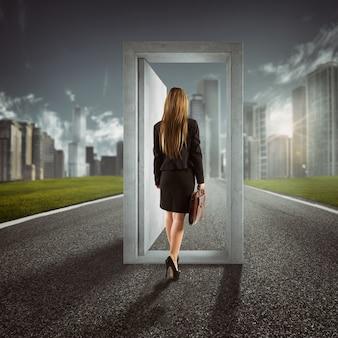 Zakenvrouw die een open deur in het midden van een weg ingaat die naar carrièresucces leidt