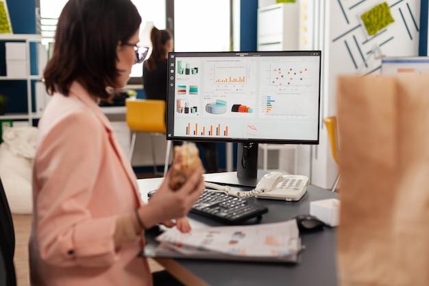 Zakenvrouw die een smakelijk broodje eet met een maaltijdpauze die in het kantoor van het bedrijf werkt tijdens de lunchpauze voor afhaalmaaltijden