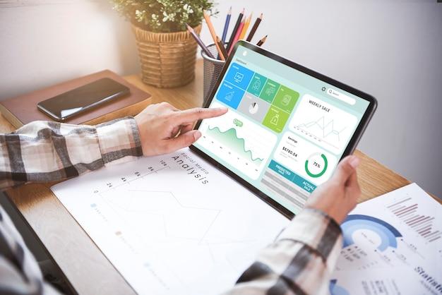Zakenvrouw die een tablet gebruikt om grafiekbedrijfsfinanciën te analyseren