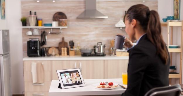 Zakenvrouw die een tablet gebruikt voor videogesprekken tijdens het ontbijt during