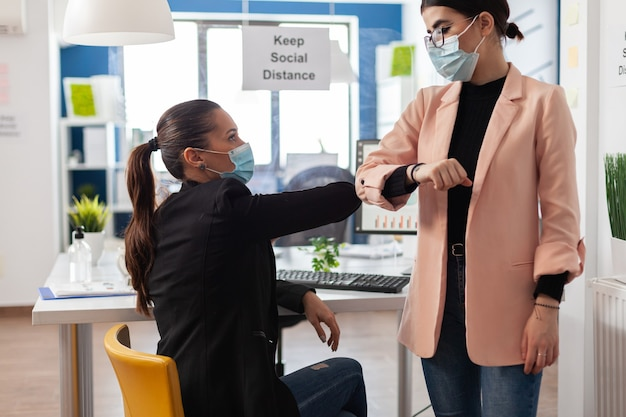 Zakenvrouw die elleboog aanraakt met manager om infectie met coronavirus te voorkomen tijdens wereldwijde pandemie. teamwork met beschermende medische gezichtsmaskers tegen covid19 die werken in een startup-kantoor