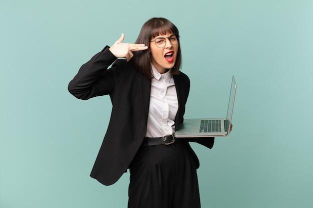 Zakenvrouw die er ongelukkig en gestrest uitziet, zelfmoordgebaar maakt een pistoolteken met de hand, wijzend naar het hoofd