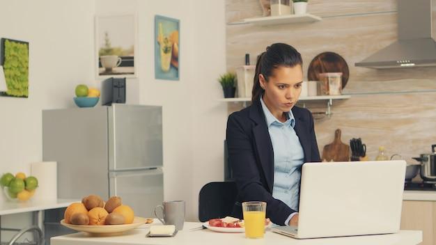 Zakenvrouw die geroosterd brood met boter eet terwijl ze aan de laptop werkt tijdens het ontbijt. geconcentreerde zakenvrouw in de ochtend multitasking in de keuken voordat ze naar kantoor gaat, stressvol met