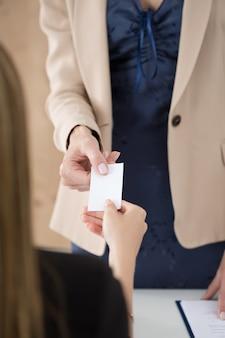 Zakenvrouw die haar visitekaartje aan haar partner geeft. zakelijke bijeenkomst, uitnodiging, partnerschap of aanwervingsconcept.
