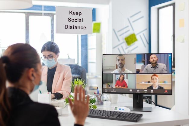Zakenvrouw die hallo zegt tijdens het verwijderen van videoconferentie op een nieuwe normale werkplek met gezichtsmasker als veiligheidsvoorzorg tijdens wereldwijde pandemie met covid10. social distancing bewaren van collega.