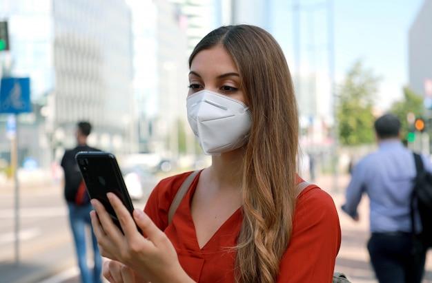 Zakenvrouw die kn95 ffp2-gezichtsmasker draagt die in moderne stadsstraat loopt met een smartphone