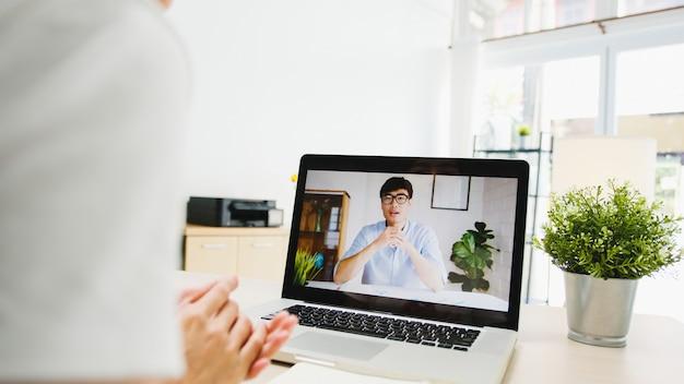Zakenvrouw die laptop gebruikt, praat met collega's over het plan in een videogesprekvergadering terwijl ze vanuit huis in de woonkamer werkt.