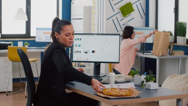Zakenvrouw die lunchtijd heeft om afhaalmaaltijden pizzapunt te eten aan de balie in het kantoor van het bedrijf en werkt bij financiële grafieken graph
