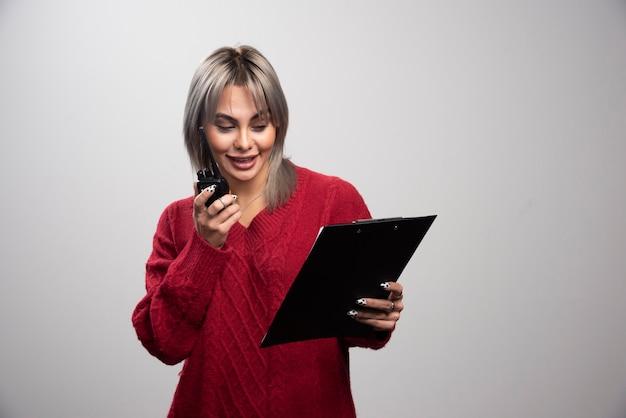 Zakenvrouw die met radiozendontvanger klembord bekijkt.