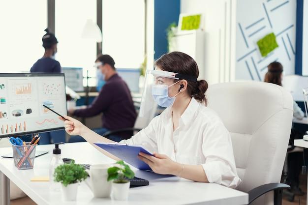 Zakenvrouw die naar financiële statistieken kijkt met een gezichtsmasker tijdens covid-19. werknemers met vizieren die in de werkruimte van een bedrijf werken, met respect voor de sociale afstand die gegevens en grafieken analyseert.