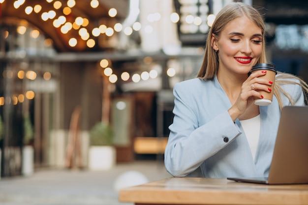Zakenvrouw die op de computer in een café werkt en koffie drinkt