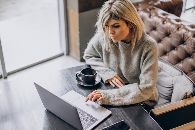 Zakenvrouw die op de computer in een café werkt