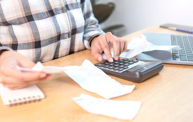 Zakenvrouw die op de rekenmachine drukt, berekent de verschillende kosten die moeten worden betaald door de rekeningen die op tafel worden gehouden en geplaatst.