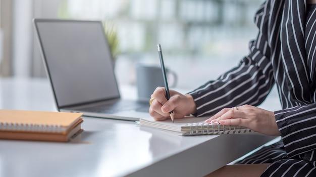 Zakenvrouw die op laptop werkt en nota neemt terwijl zittend aan de tafel op kantoor