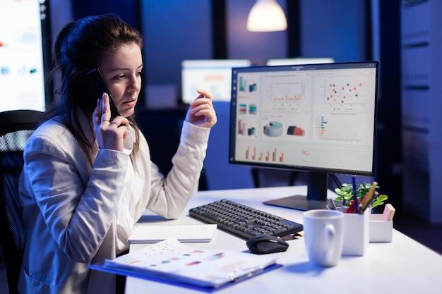 Zakenvrouw die op smartphone spreekt met haar teamgenoot terwijl ze op de computer werkt met grafische financiële statistieken