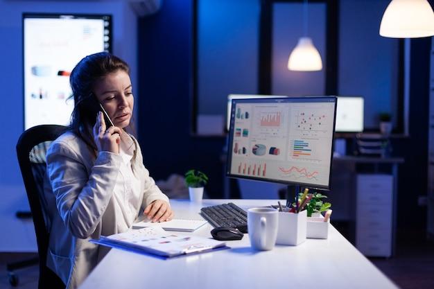 Zakenvrouw die op smartphone spreekt met haar teamgenoot terwijl ze op de computer werkt