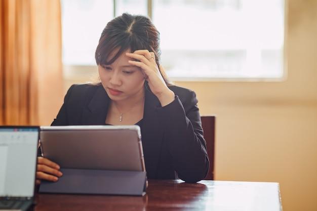 Zakenvrouw die op tablet werkt met stress-emotie