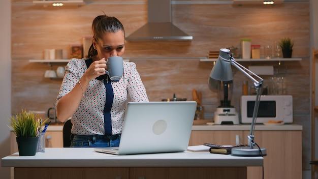 Zakenvrouw die 's avonds laat thuis werkt en op laptop schrijft en koffie drinkt. drukke, gefocuste werknemer die moderne technologienetwerken draadloos gebruikt om overuren te maken voor lezen, typen, zoeken