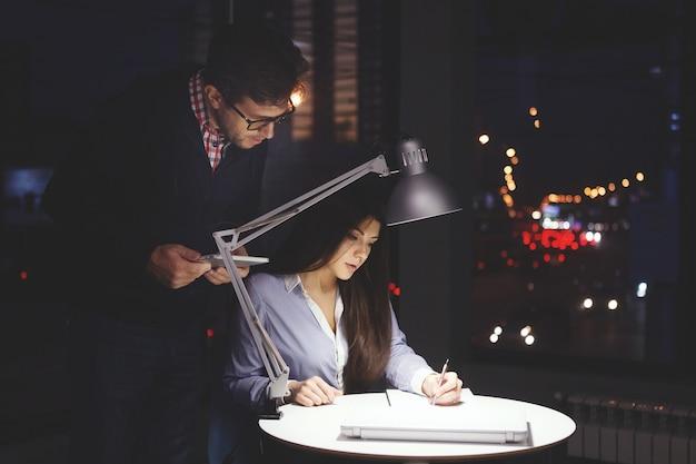 Zakenvrouw die 's nachts op kantoor aan de tafel werkt met een bureaulamp een bebaarde man met een bril staat achter haar rug en helpt met advies buiten het raam zijn veelkleurige lichten aangestoken