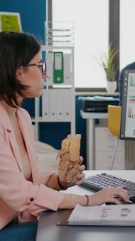 Zakenvrouw die smakelijke sandwich eet met een maaltijdpauze die in een zakelijk bedrijf werkt