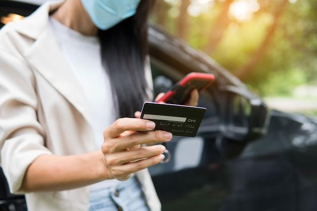 Zakenvrouw die smartphone en creditcard gebruikt om online in de auto te winkelen. zakelijk nieuw normaal concept na uitbraak van covid-19 coronavirus.