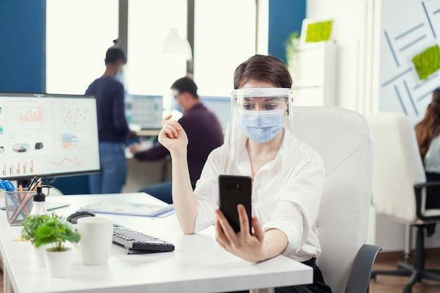 Zakenvrouw die smartphone gebruikt voor videogesprek op de werkplek met gezicht als veiligheidsmaatregel. collega's die werken met respect voor sociale afstand tijdens wereldwijde pandemie met coronavirus.