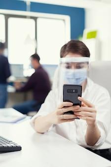 Zakenvrouw die sms't met een mobiele telefoon op een smartphone met een gezichtsmasker als veiligheidsmaatregel tegen covid19. multi-etnische collega's die werken met respect voor sociale afstand in een financieel bedrijf.