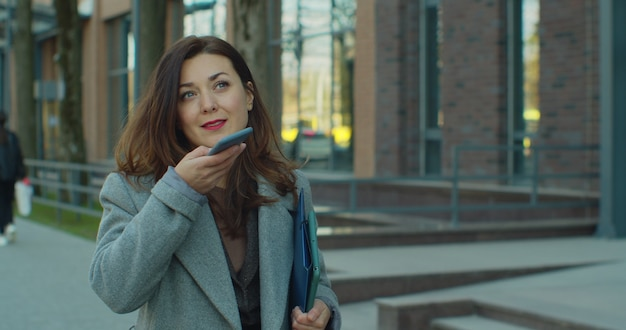 Zakenvrouw die spraakbericht verzendt op smartphone loopt in de buurt van modern kantoor