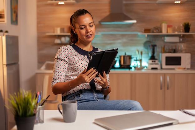Zakenvrouw die tablet-pc gebruikt terwijl ze vanuit huis werkt, keukenmedewerker die moderne technologie gebruikt bij mi...
