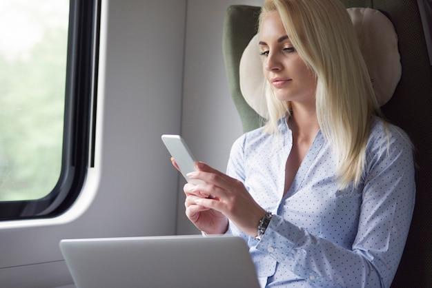 Zakenvrouw die tijdens de reis door mobiele apparaten werkt