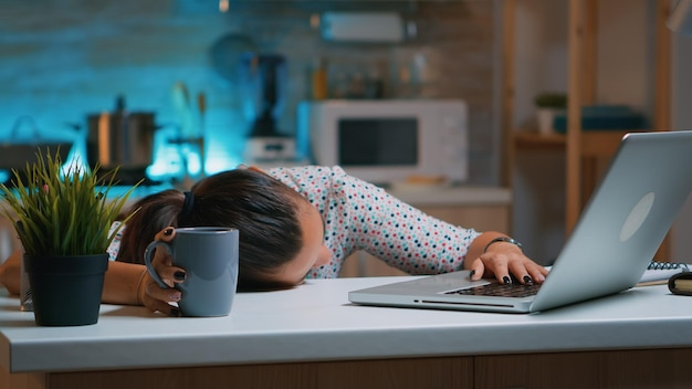 Zakenvrouw die tot middernacht aan het project werkte en in slaap viel op een bureau dat thuis werkte met de hand op het toetsenbord. werknemer met behulp van moderne technologie netwerk draadloos doen overuren slapen op tafel.
