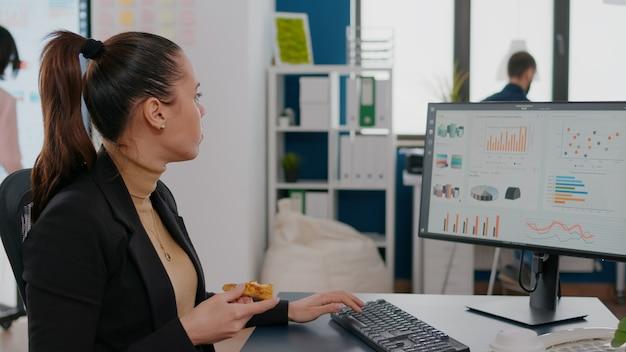 Zakenvrouw die voedselbestelling op het bureau heeft tijdens afhaallunch die in het kantoor van het bedrijf werkt
