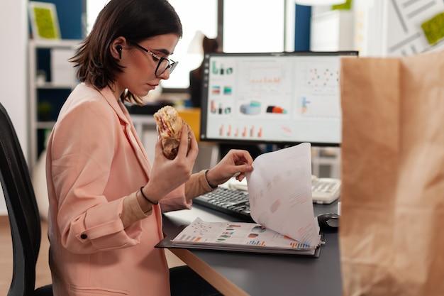 Zakenvrouw die werkt in het kantoor van een opstartend bedrijf met eten maaltijd afhalen lunchtijd lekker eten