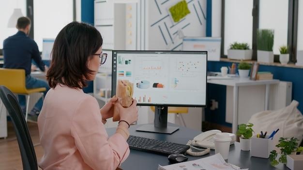 Zakenvrouw die werkt in het kantoor van een opstartend bedrijf met lunch voor afhaalmaaltijden