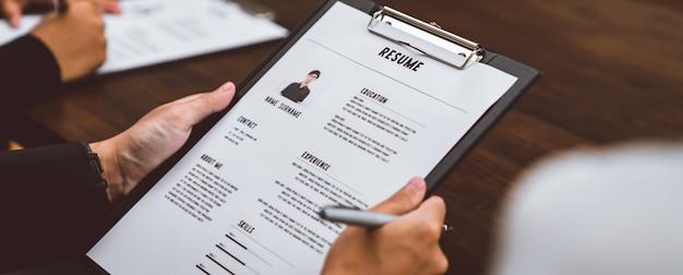Zakenvrouw dient cv-werkgever in om sollicitatie-informatie op het bureau te bekijken, biedt het bedrijf de mogelijkheid om akkoord te gaan met de positie van de baan