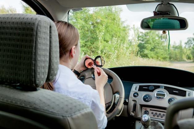 Zakenvrouw doet make-up tijdens het besturen van een auto in de file