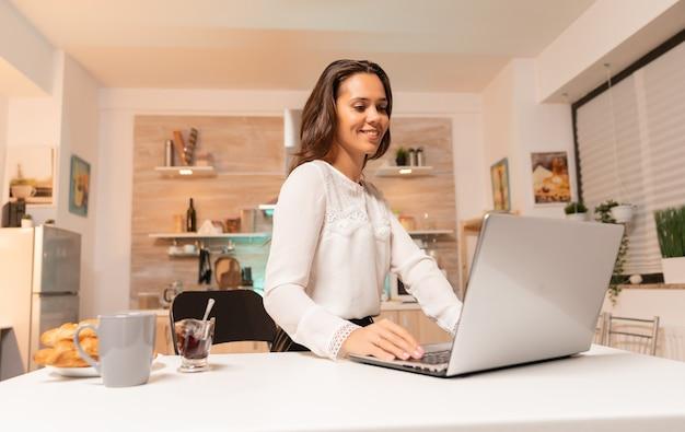 Zakenvrouw doet overuren die aan laptop in huisuitrusting werken om zaken te laten groeien. geconcentreerde lachende ondernemer in huiskeuken met behulp van notebook tijdens de late uurtjes in de avond.