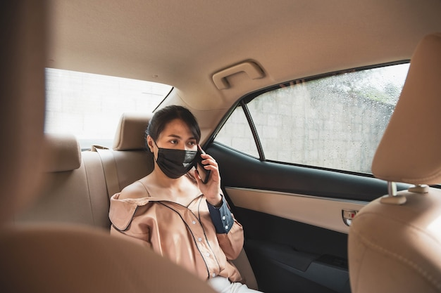 Zakenvrouw draagt beschermend gezichtsmasker praten via de mobiele telefoon zittend op de achterbank in de auto