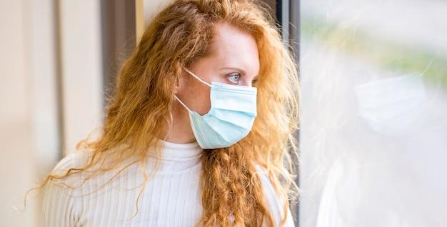Zakenvrouw draagt een masker en kijkt buiten het raam