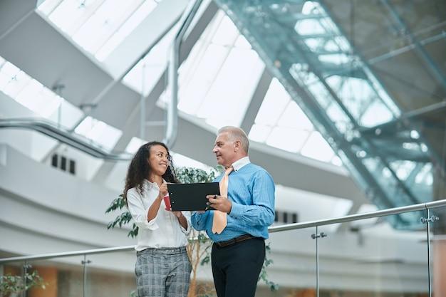 Zakenvrouw en een zakenman die zakelijke documenten bespreken