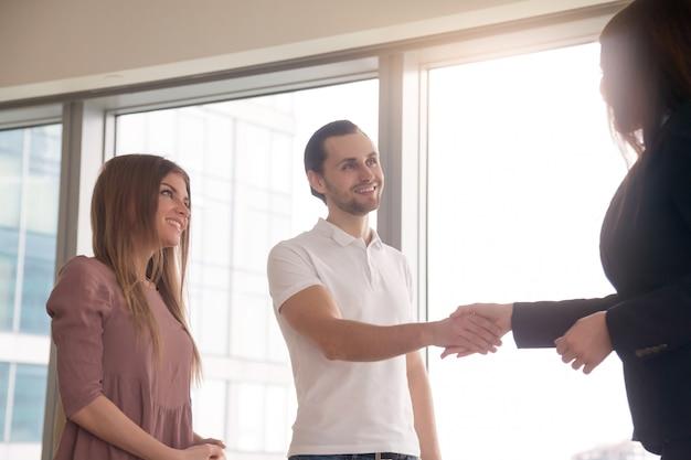 Zakenvrouw en klanten handen schudden op zakelijke bijeenkomst, groet handdruk